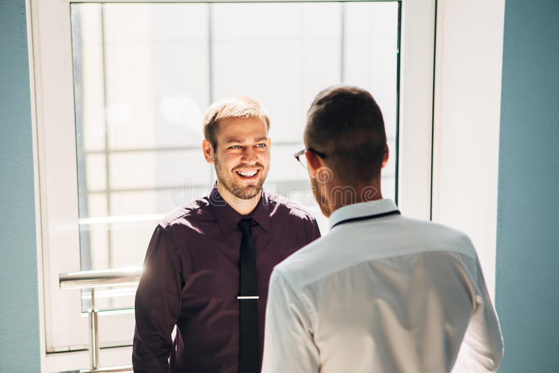 Zwei Männer, die in der Lobby des Büros sprechen lizenzfreie stockfotografie