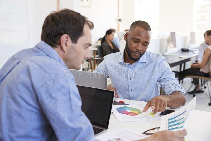 Zwei Männer, die Dokumente in einem beschäftigten Büro besprechen lizenzfreie stockbilder