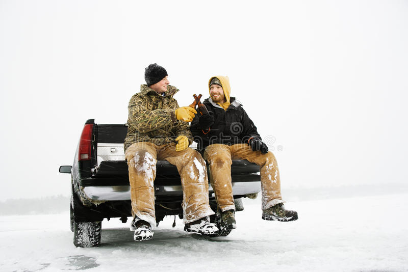 Zwei Männer, die ein Bier auf LKW essen lizenzfreie stockfotos