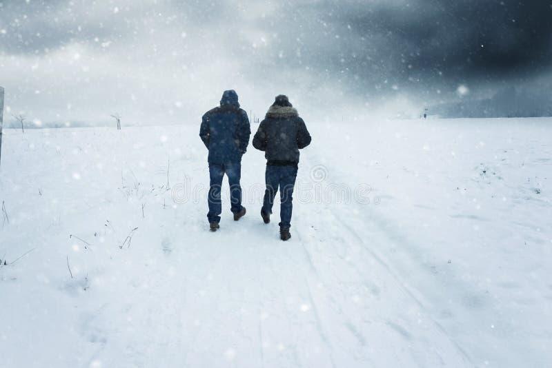 Zwei Männer, die entlang den schneebedeckten Fußweg im stürmischen Wetter gehen stockfotos