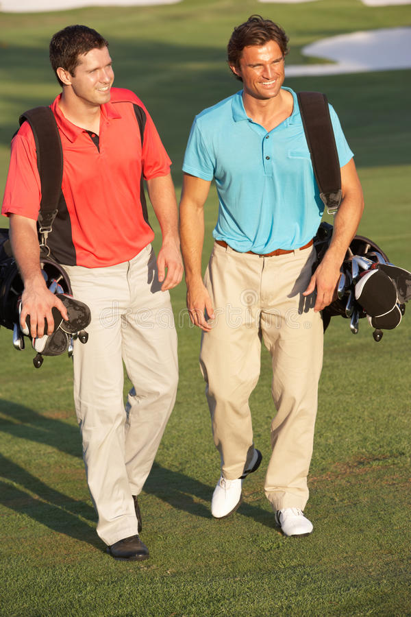 Zwei Männer, die entlang Golfplatz gehen stockfotografie