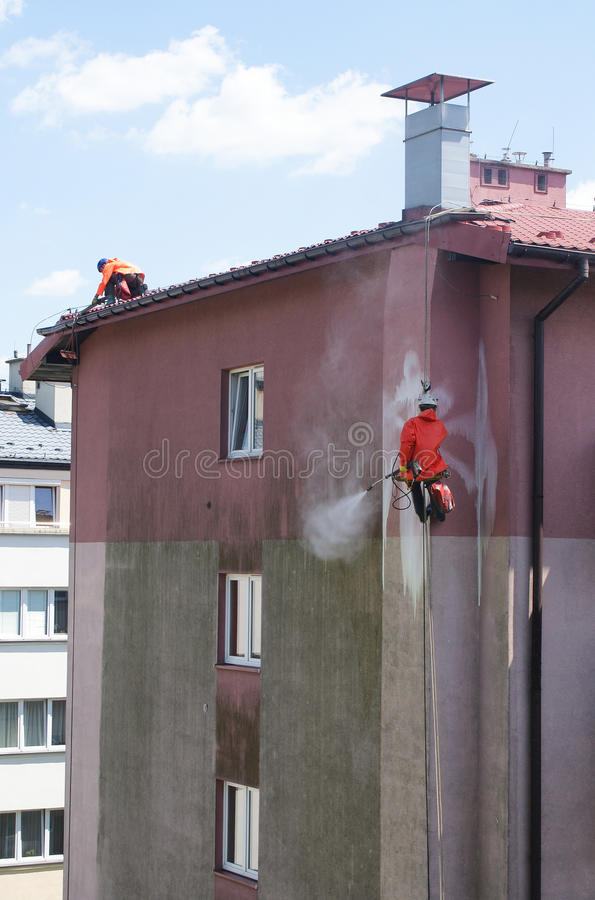 Zwei Männer, die Gebäudewand säubern stockfotos