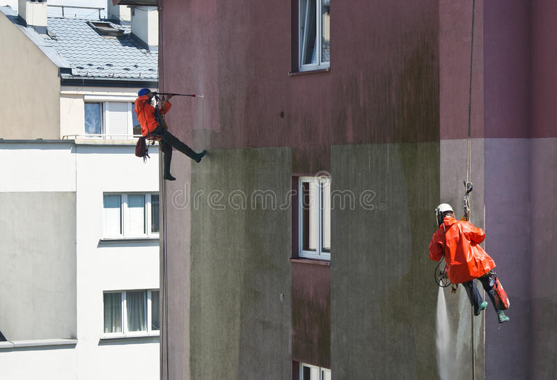 Zwei Männer, die Gebäudewand säubern stockbilder