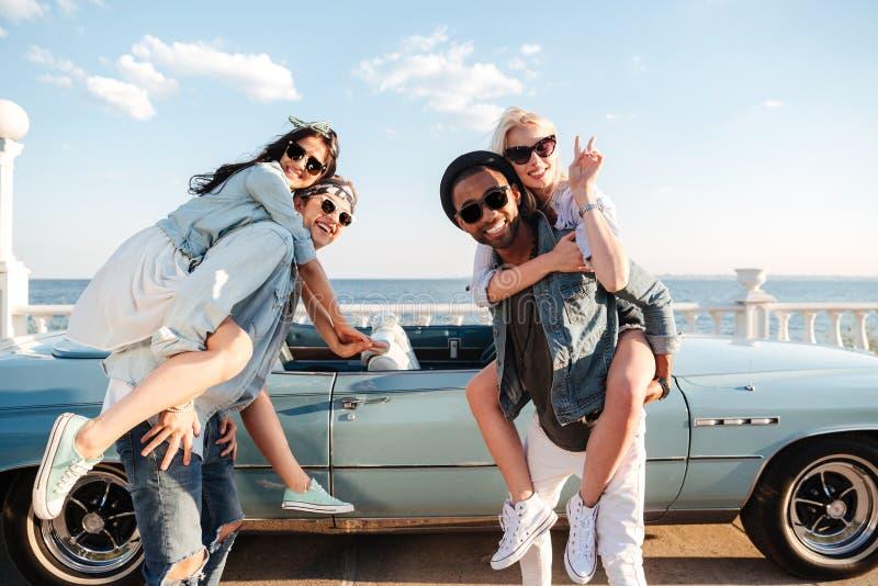Zwei Männer, die ihre Freundinnen halten und im Sommer lächeln lizenzfreie stockfotografie