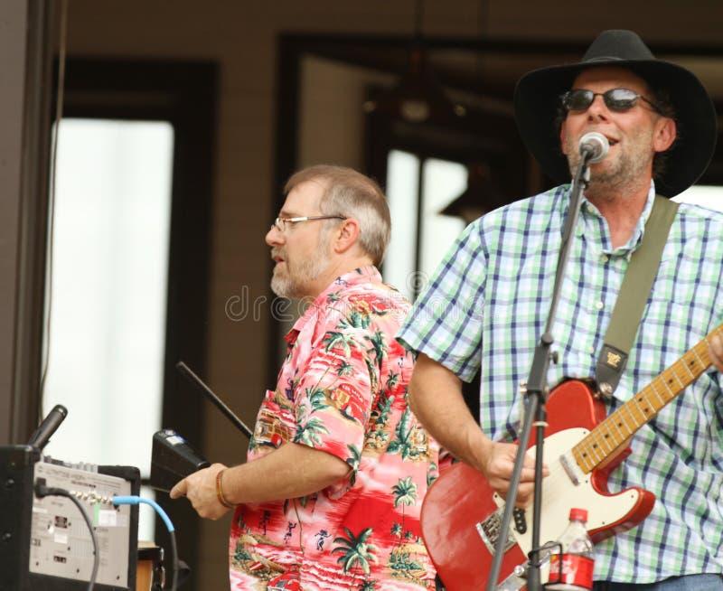 Zwei Männer, die Kuhglocke und -E-Gitarre während eines Konzerts im Freien spielen lizenzfreie stockbilder