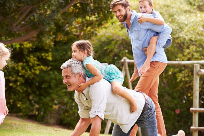 Zwei Männer, die mit Kindern in einem Garten spielen stockbild