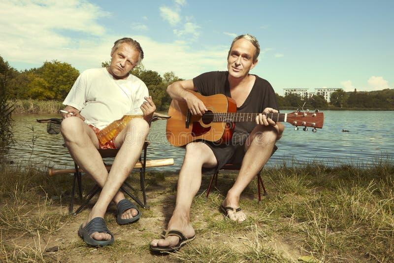 Zwei Männer, die Sommertag auf Wiese durch den See mit Gitarre genießen lizenzfreie stockfotografie