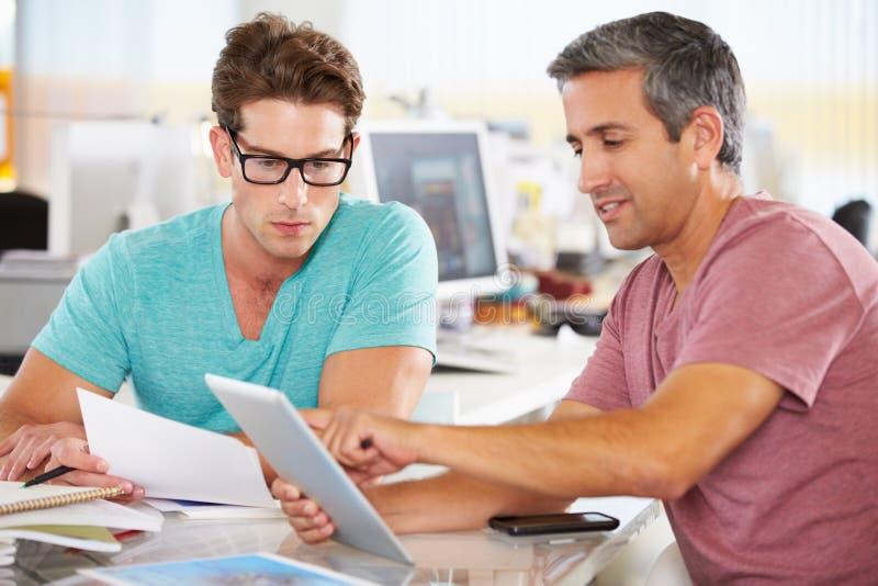 Zwei Männer, die Tablette-Computer im kreativen Büro verwenden lizenzfreie stockbilder