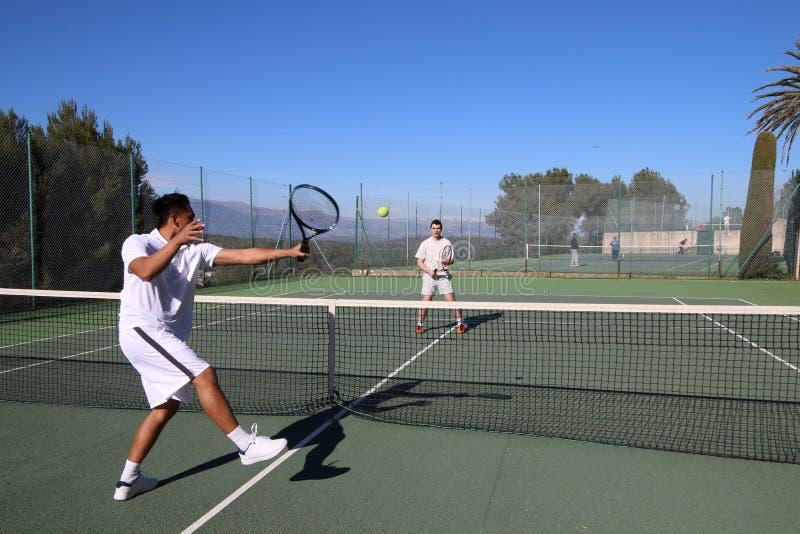 Zwei Männer, die Tennis im Sommer spielen stockbild