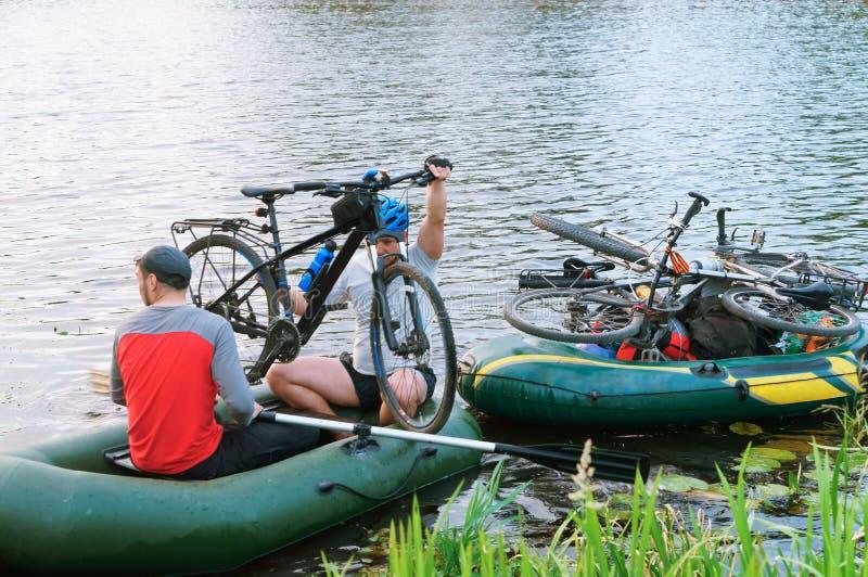 Zwei Männer in einem Boot mit Fahrrädern am 11. Juni 2018 Kaliningrad-Region, Russland, Reisende auf der Bootskreuzung, den Fluss stockfotografie