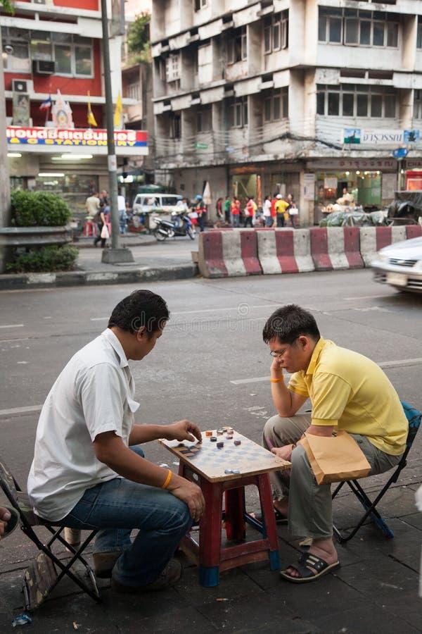 Zwei Männer genießen, Kontrolleure mit den Flaschenkapseln zu spielen, die tagsüber auf einer lauten Straße in Bangkok sitzen stockfotografie