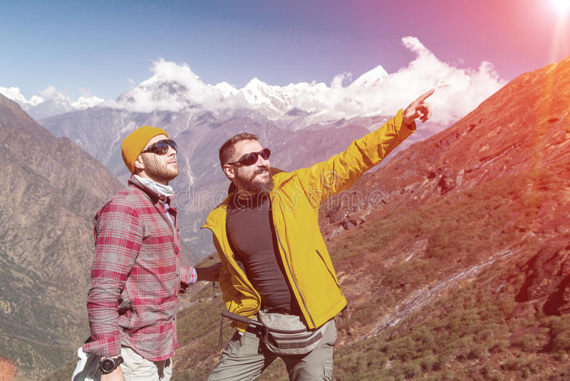 Zwei Männer im Freien, die auf dem Gebirgspfadzeigen im altem Stil bleiben stockbilder