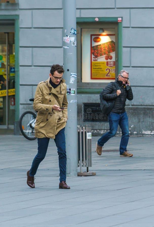 Zwei Männer mit Handys in den Händen auf Hauptplatz, Graz, Österreich stockbild
