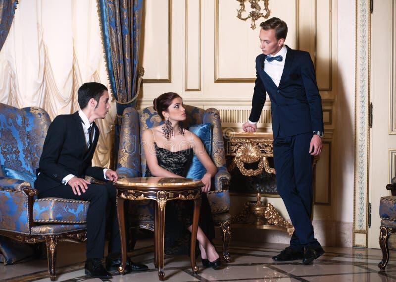 Zwei Männer und Frau, die im Luxuxinnenraum sich unterhalten stockfotos