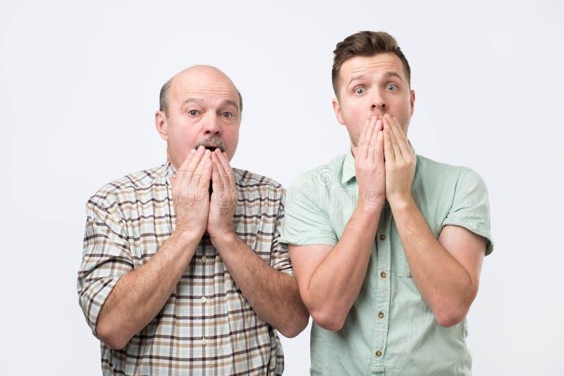 Zwei Männer unterschiedliche Generation uexpected Anstarren an der Kamera können nicht an schockierende Gerüchte glauben lizenzfreie stockfotografie
