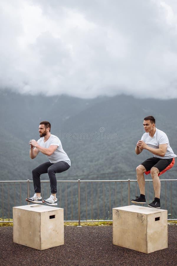 Zwei männliche athletische Freunde, die Kasten tun, springen im Freien auf den Berg stockfotos