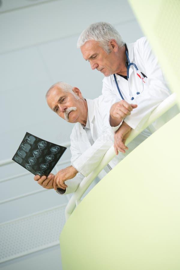 Zwei männliche Doktoren, die Röntgenstrahlbild überprüfen stockfotografie