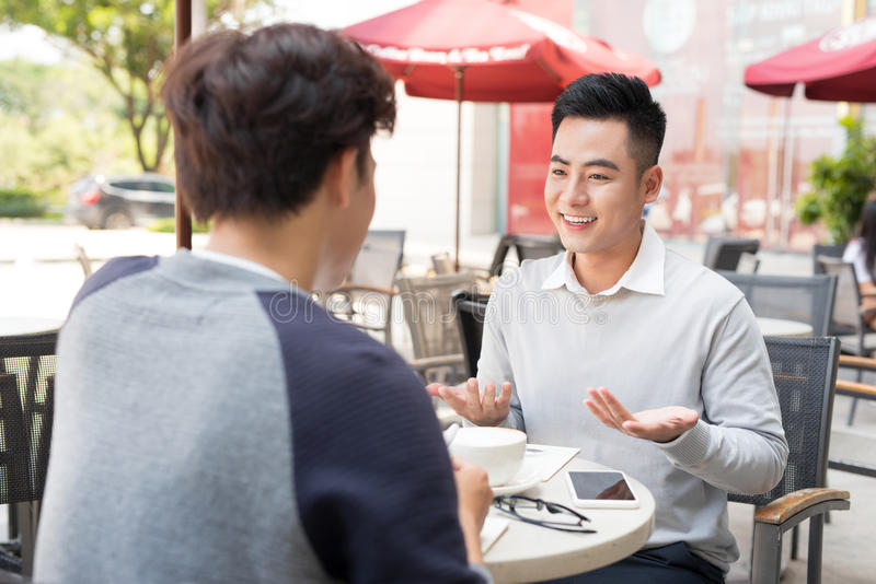 Zwei männliche Geschäftsmänner, die im Café sitzen und das Geschäft Pro besprechen stockfotografie
