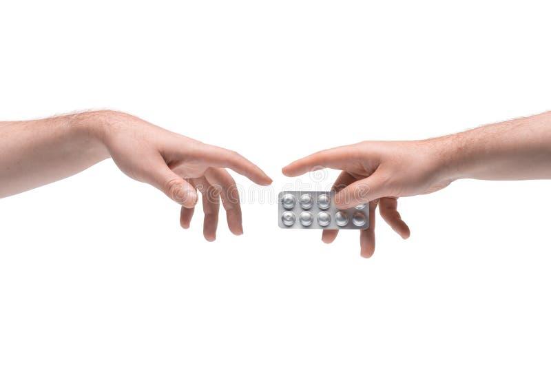 Zwei männliche Hände, die sich eine weitere Pillenpackung auf weißem Grund geben lizenzfreie stockfotos