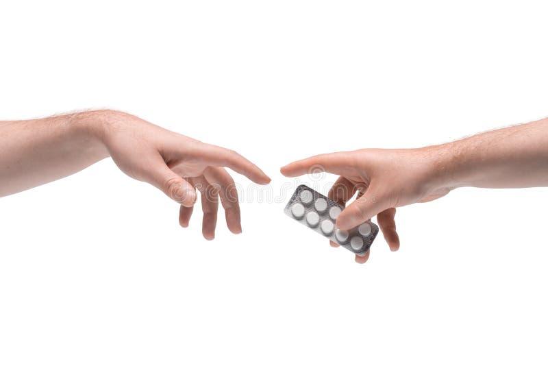 Zwei männliche Hände, die sich eine weitere Pillenpackung auf weißem Grund geben lizenzfreies stockbild
