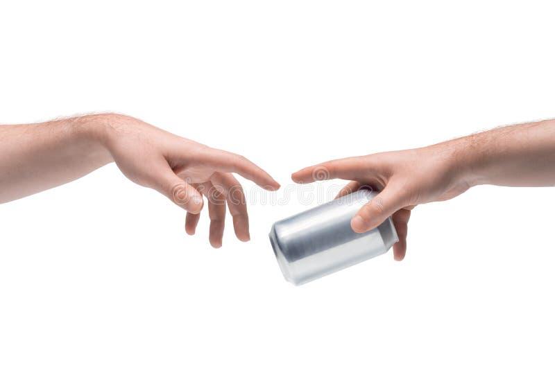 Zwei männliche Hände, die sich gegenseitig eine leere metallische Soda-Dose auf weißem Hintergrund abgeben lizenzfreies stockfoto