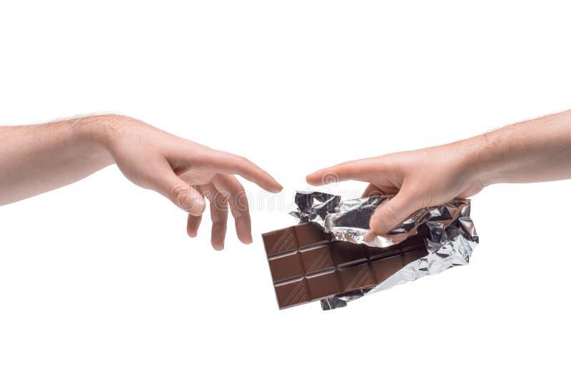 Zwei männliche Hände, die sich gegenseitig Schokoladenriegel in Folie mit weißem Hintergrund übergeben lizenzfreie stockbilder