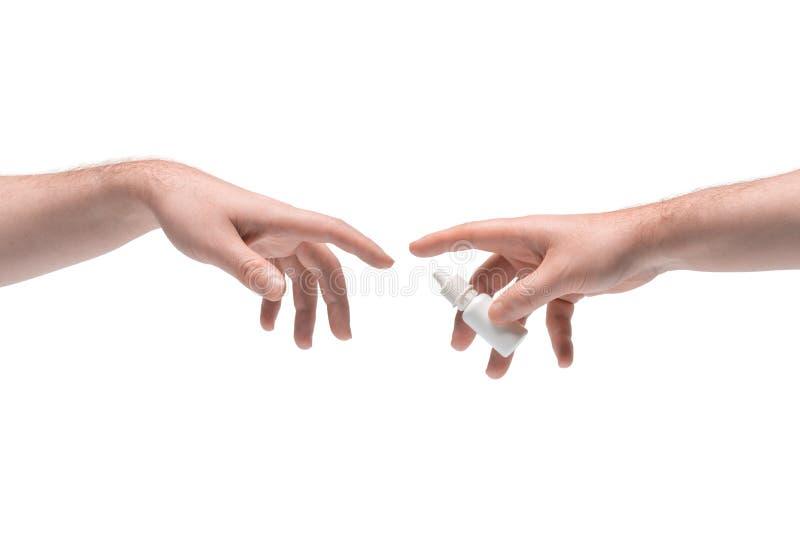 Zwei männliche Hände, die sich gegenseitig weiße kleine Plastikleuchte mit Nasenspray auf weißem Hintergrund geben stockbilder
