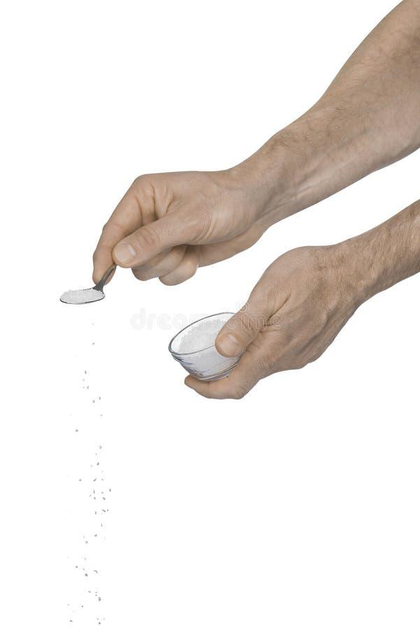 Zwei männliche Hände, die zerquetschtes Salz unter Verwendung eines Teelöffels hinzufügen stockbilder