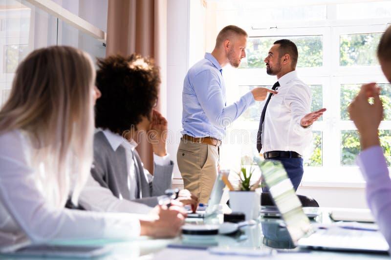 Zwei männliche Kollegen, die im Büro kämpfen stockfotos