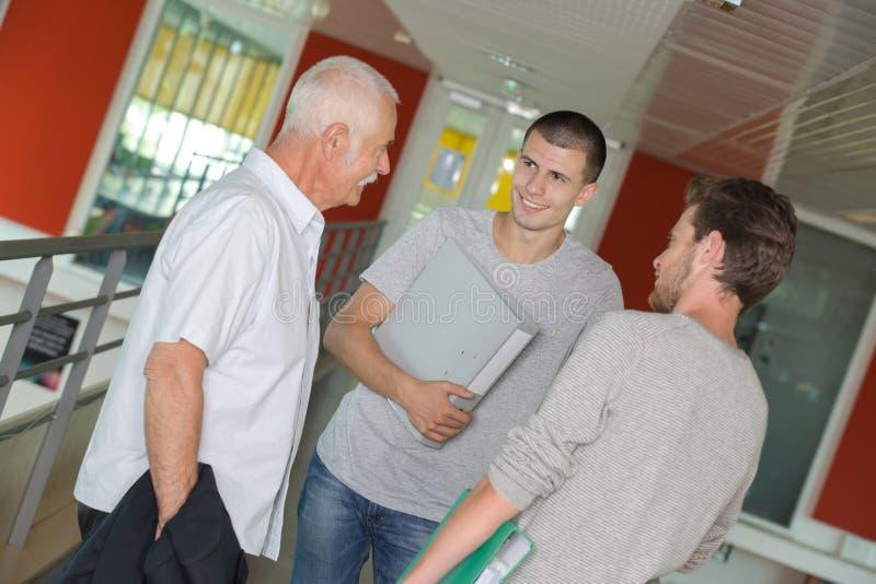 Zwei m?nnliche Studenten, die mit ?lterem Lehrer im Korridor plaudern lizenzfreies stockfoto