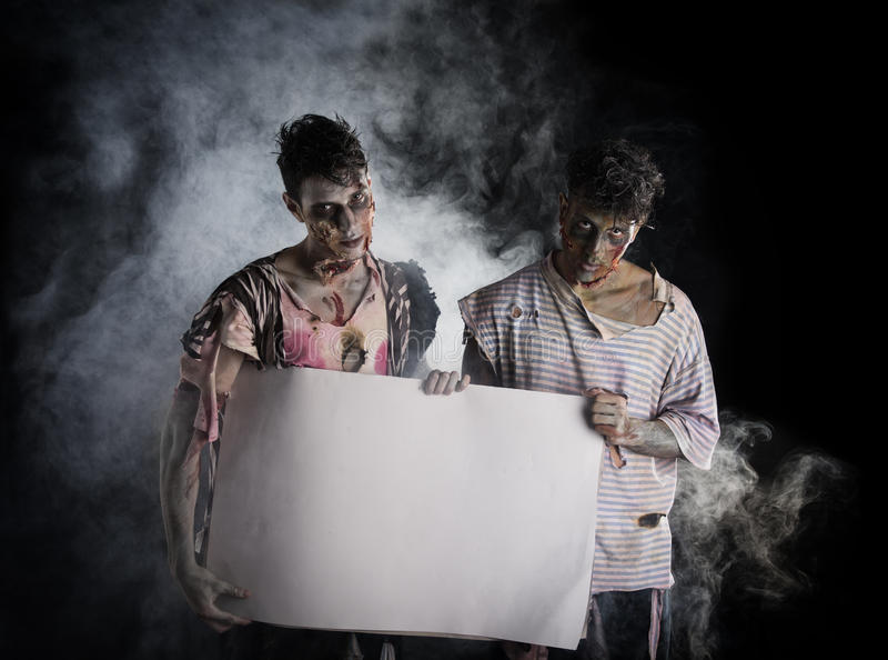 Zwei männliche Zombies, die leere weiße Fahne halten lizenzfreie stockbilder