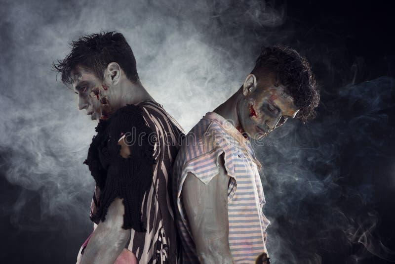 Zwei männliche Zombies zurück zu Rückseite auf schwarzem rauchigem Hintergrund stockfotos