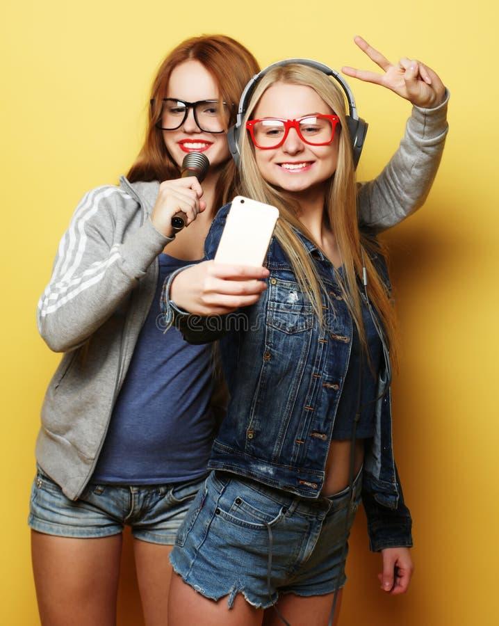 Zwei M?dchen mit einem Mikrofon Spa? zusammen singend und habend, machen selfie stockbild