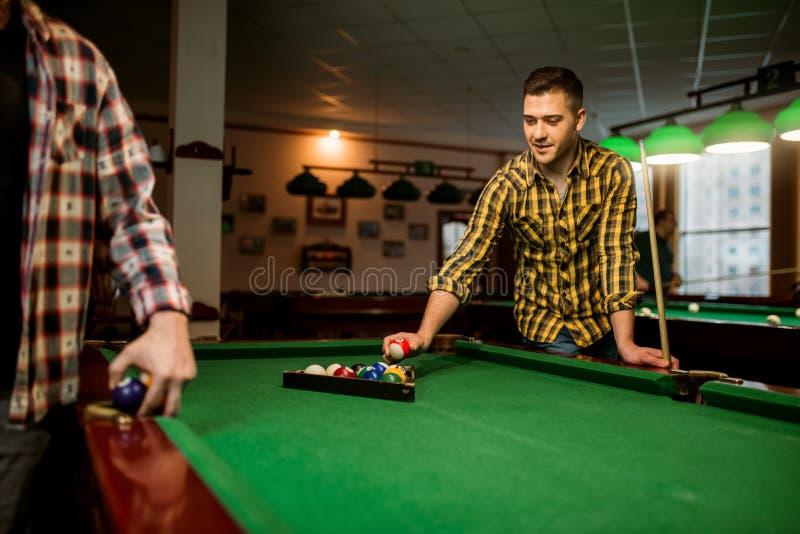 Zwei m?nnliche Billiardspieler setzt bunte B?lle stockbild