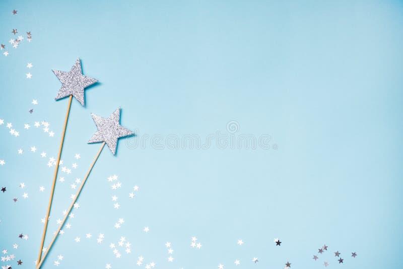 Zwei magische Stäbe der silbernen Partei und zerstreute Paillette auf einem blauen Hintergrund Kopieren Sie Platz stockfotografie