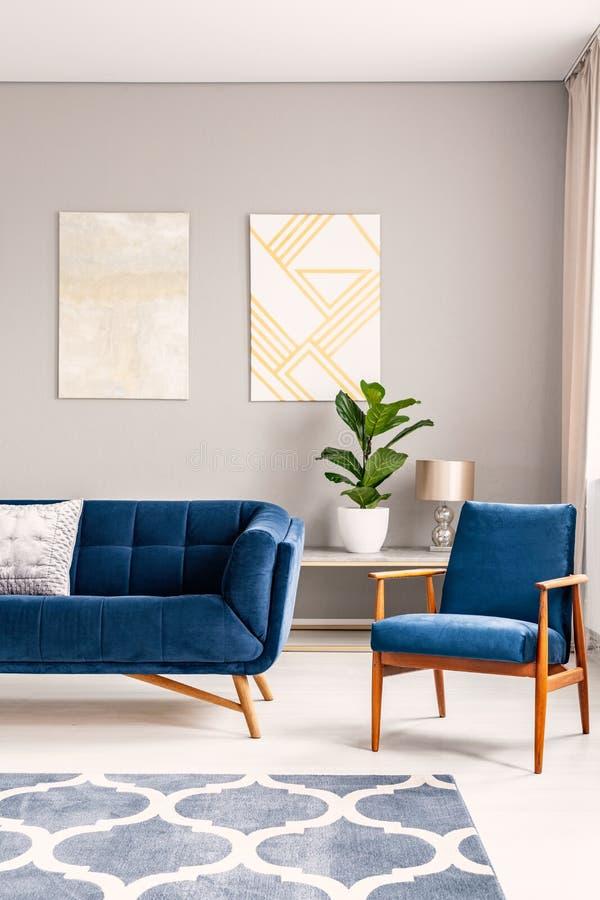 Zwei Malereien der modernen Kunst, die an der Wand im wirklichen Foto des hellen Wohnzimmerinnenraums mit blauer Couch und Lehnse lizenzfreie stockfotos