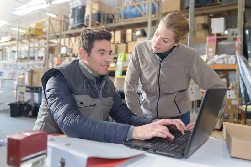 Zwei Manager, die an Laptop im Lager arbeiten stockfoto