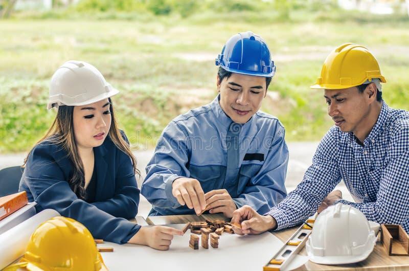 Zwei-mann Frauenarchitekt zeichnet einen Plan, auf großem Blatt Papier am Schreibtisch und baut Musterhaus von den Holzklotzstang lizenzfreie stockfotos