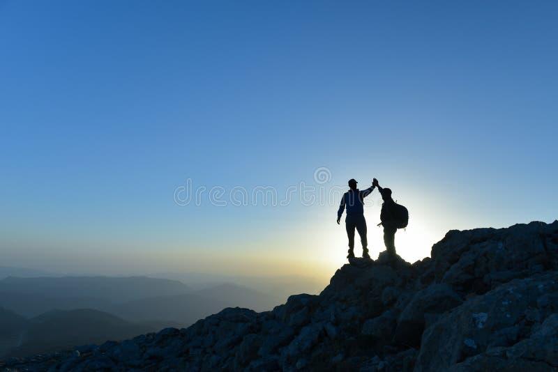 Zwei-mann mit Erfolgsgeste auf Berg lizenzfreie stockfotos