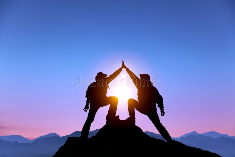 Zwei-mann mit Erfolgsgeste auf dem Berg stockbild