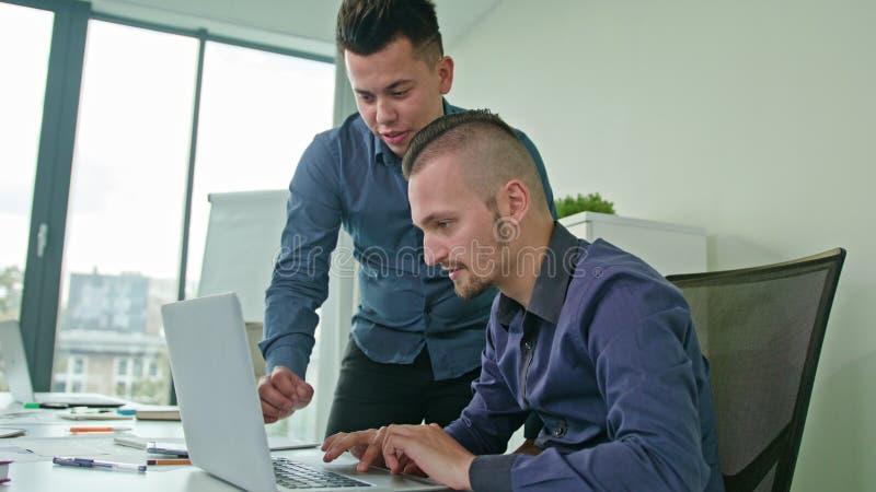 Zwei-manndiskussionsideen unter Verwendung des Laptops stockfotografie