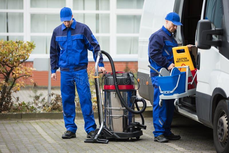 Zwei Manneshausmeister Unloading Cleaning Equipment vom Fahrzeug lizenzfreies stockbild