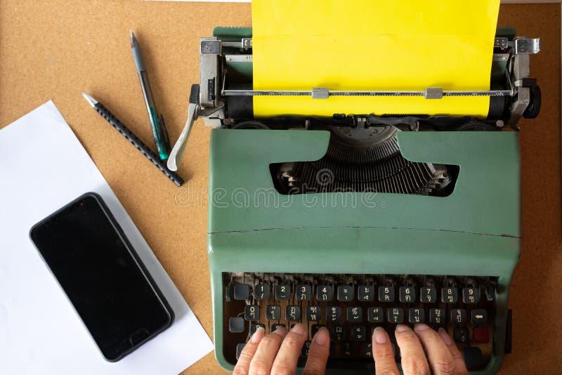 Zwei-mannhand, die auf alter tadelloser grüner thailändischer Schreibmaschine der Weinlese mit einfachem gelbem Papier schreibt lizenzfreies stockbild