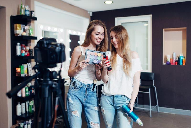 Zwei Maskenbildner, die neue Schönheitsprodukte in ihrem Studio annoncierend lachen stockfotos