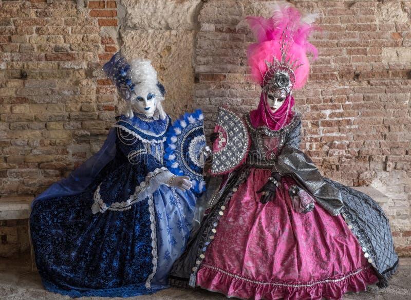 Zwei maskierten die Frauen, die nach innen auf einer Steinbank während Venedig-Karnevals sitzen lizenzfreie stockfotos