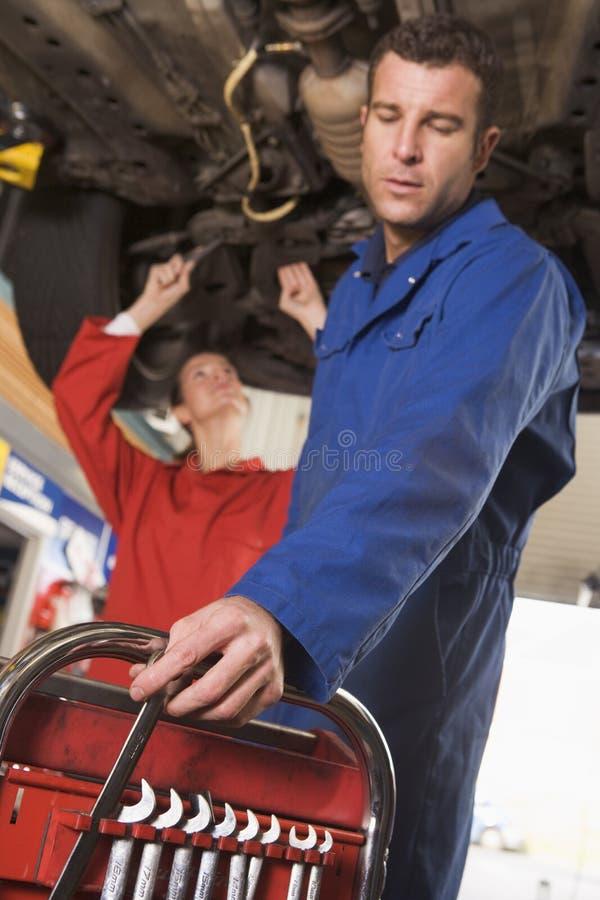 Zwei Mechaniker, die unter Auto arbeiten stockbild