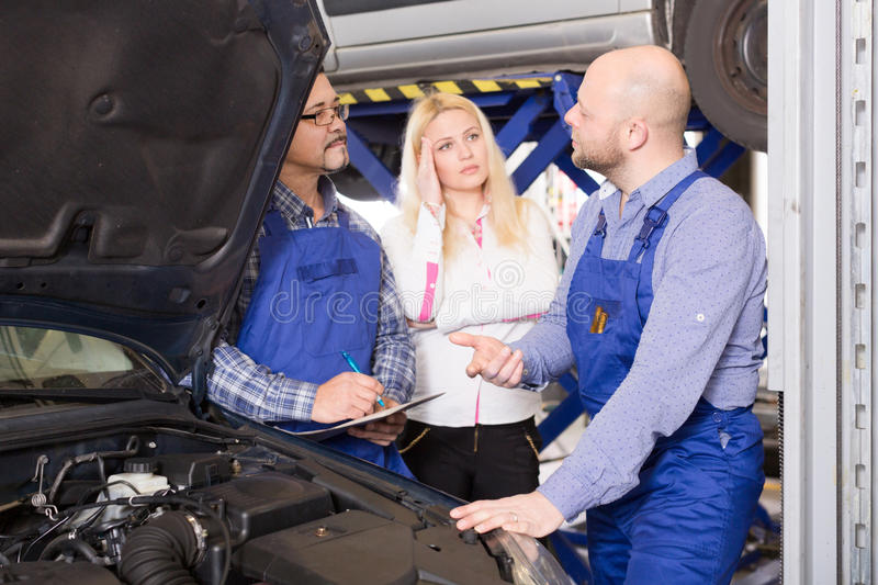 Zwei Mechaniker, die versuchen, Kunden an der Werkstatt zu betrügen lizenzfreie stockfotografie