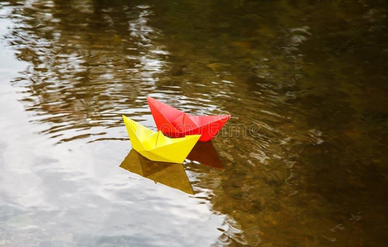 Zwei mehrfarbige Papierboote, die auf einen Strom schwimmen lizenzfreie stockfotos