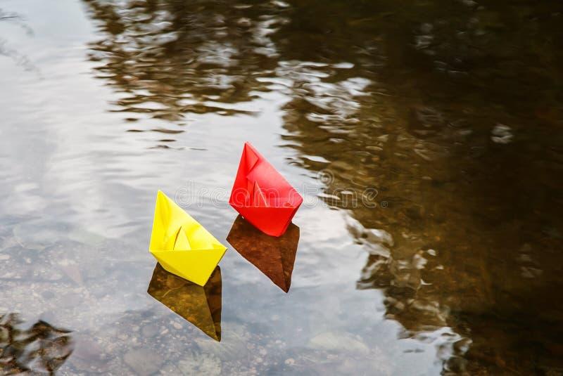 Zwei mehrfarbige Papierboote, die auf einen Strom schwimmen stockbild