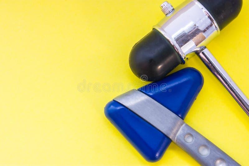 Zwei Metallneurologische Gummihämmer, zum oder Test auf Nervenreflexen zu überprüfen sind auf Draufsicht des gelben Hintergrundes lizenzfreies stockbild